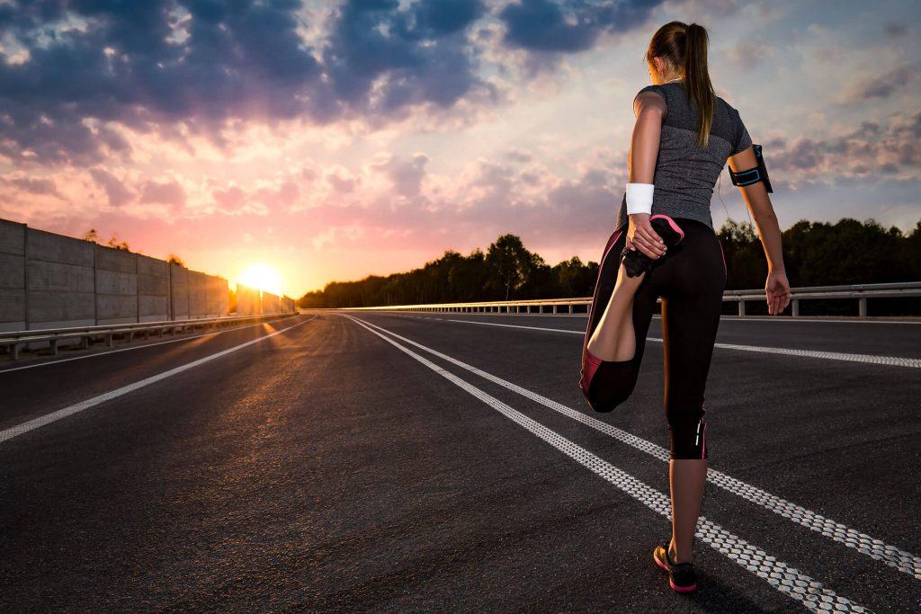 Frau beim Dehnen auf Straße mit Sonnenuntergang
