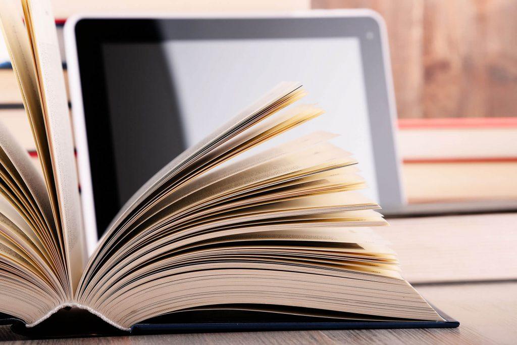 Aufgeschlagenes Buch und Laptop